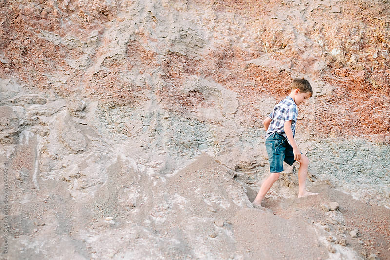 Boy in summer clothes walking in front of red rock cliff by Rebecca Spencer for Stocksy United