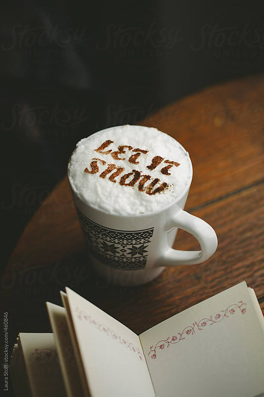 Hot chocolate mug with words Let it snow written with cacao powder on cream and book by Laura Stolfi for Stocksy United