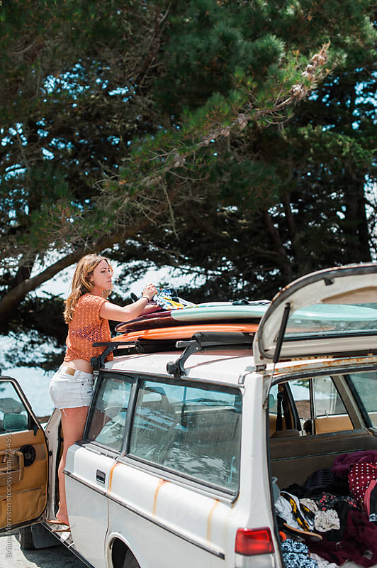 Young Woman Tying Surfboards to the Roof of a Retro Wagon by Briana Morrison for Stocksy United