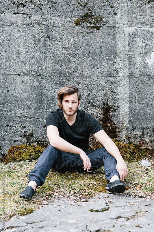 Young man seated against cement wall on grass by Amir Kaljikovic for Stocksy United
