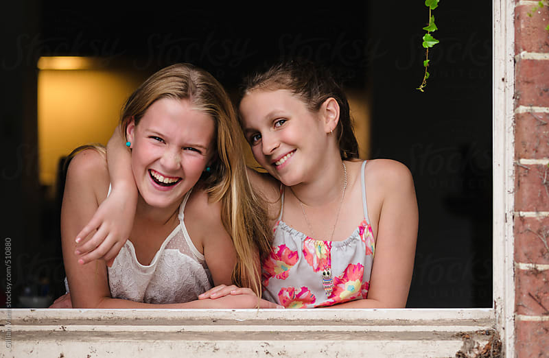 girls laughing together, hanging out a window by Gillian Vann for Stocksy United