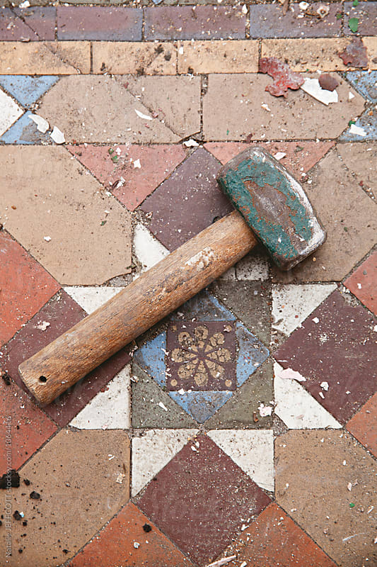 Close up of hammer on old tiles by Natalie JEFFCOTT for Stocksy United