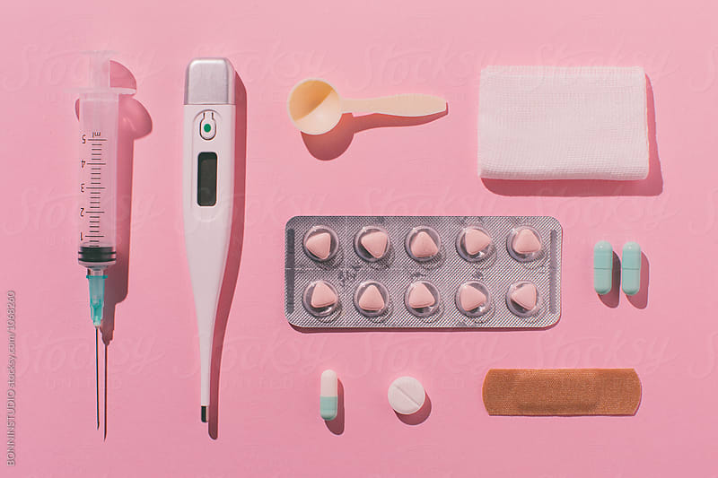Still life of medical supplies on pink background.
