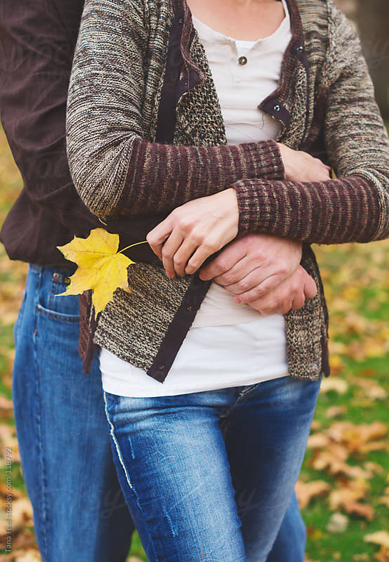 A woman holds a leaf while being held in a loving hug by Tana Teel for Stocksy United
