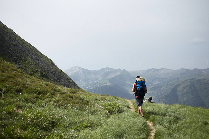 Young backpacker in a high trail of the Pyrenees by Miquel Llonch for Stocksy United