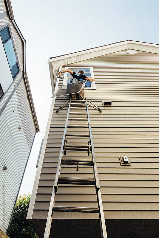 Window Washer On Top Of Tall Ladder Cleaning Fourth Story Window