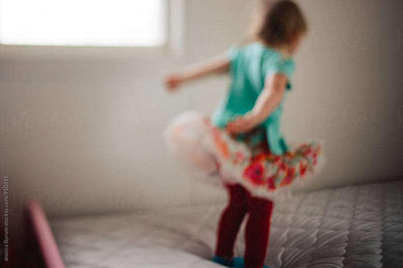 Little girl jumping on bed by Jessica Byrum for Stocksy United