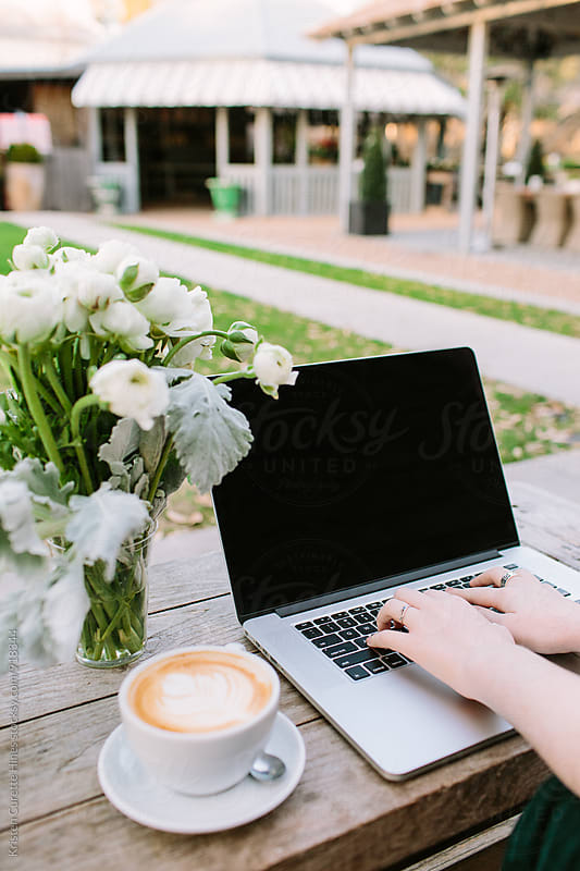 A woman sitting outdoors drinking a latte and typing in a laptop by Kristen Curette Hines for Stocksy United