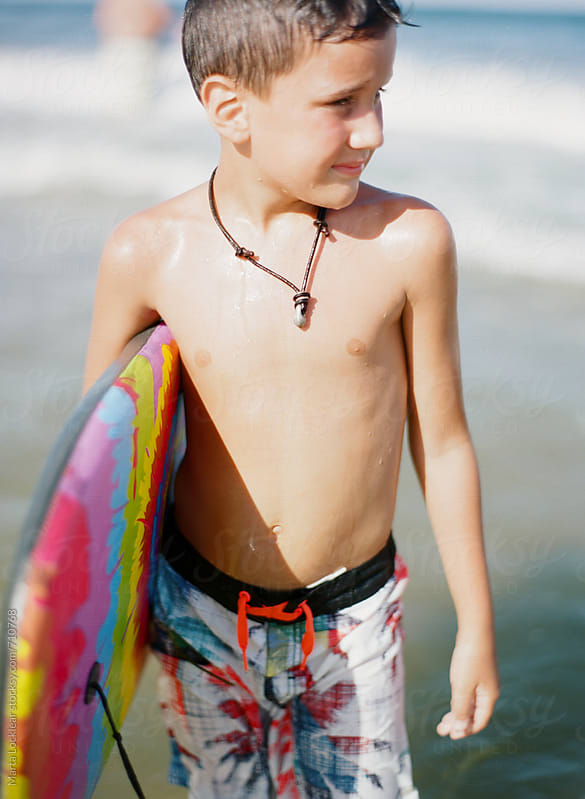 Boy holding a boogie board at the beach by Marta Locklear for Stocksy United
