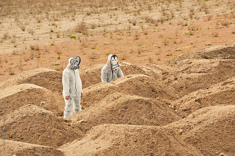 Mask Monster - People with selfmade masks in white overalls standing inbetween sandy hills by Urs Siedentop & Co for Stocksy United