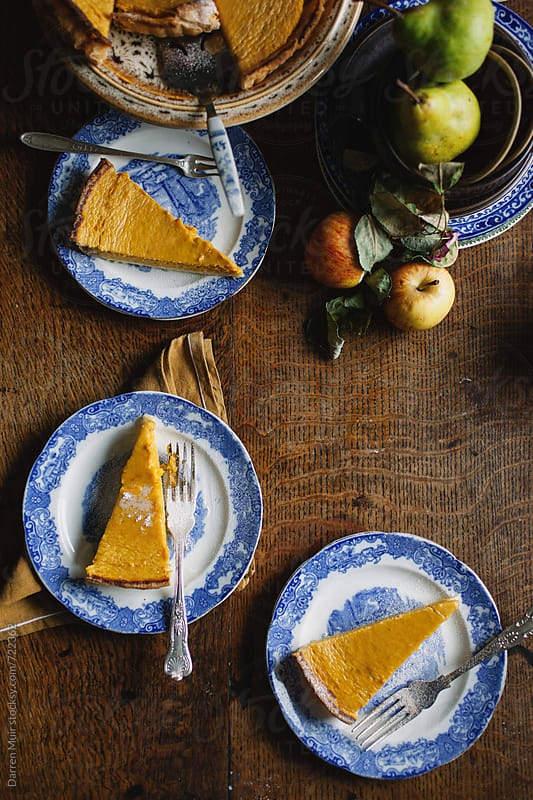 Slices of homemade pumpkin pie seen from above on a wooden table. by Darren Muir for Stocksy United