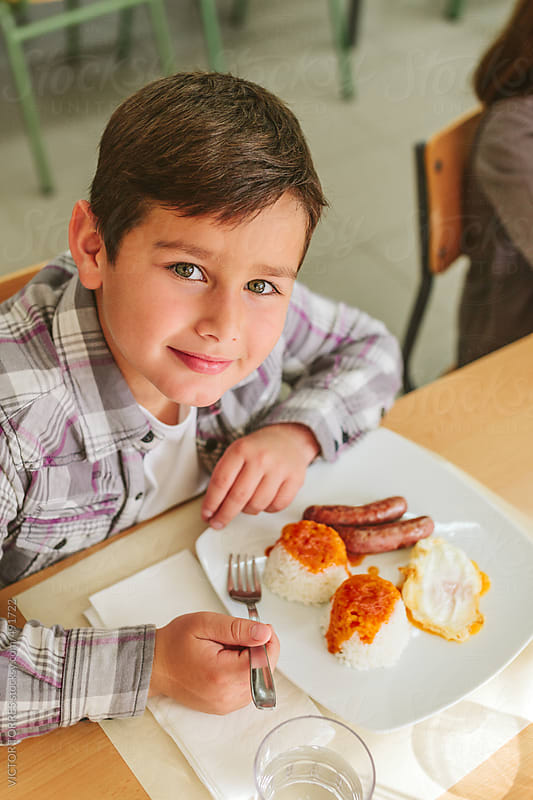 Cute Kid Eating at the School Canteen by VICTOR TORRES for Stocksy United