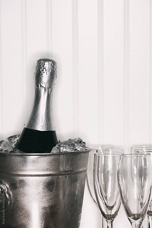NYE: Bottle Of Champagne Chilling With Glasses In Front Of Beadboard by Sean Locke for Stocksy United