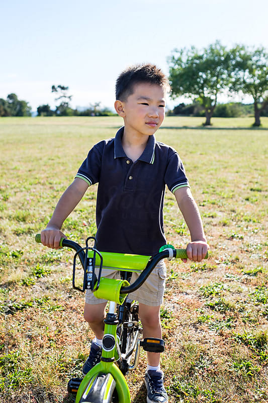 Happy Asian boy biking in the park by Suprijono Suharjoto for Stocksy United