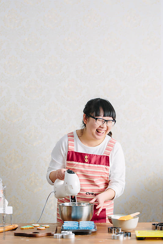 Young Chinese woman using electric whisk by MaaHoo Studio for Stocksy United