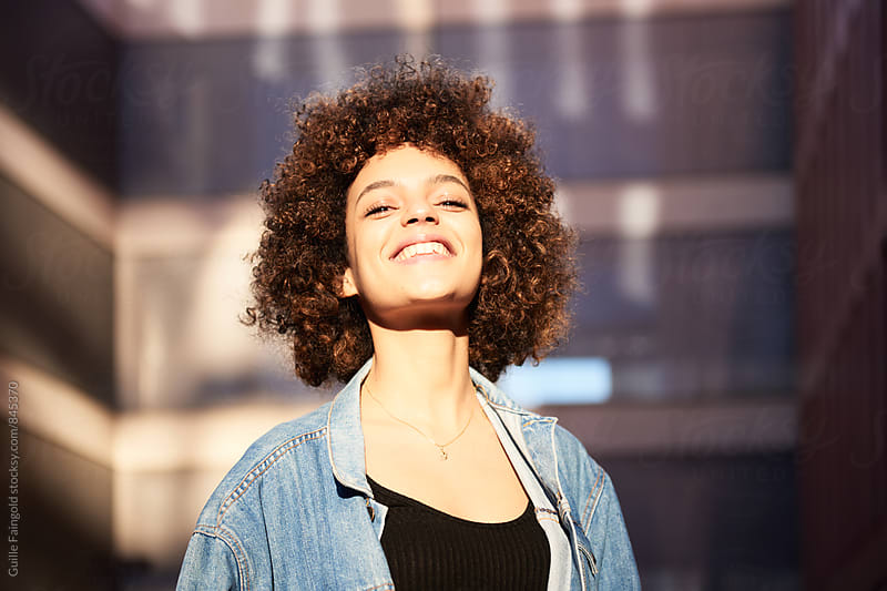 Close-up of beautiful smiling woman with afro by Guille Faingold for Stocksy United