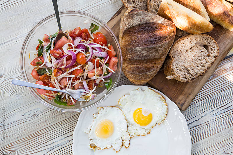Fried eggs, bread and sald breakfast by Lior + Lone for Stocksy United
