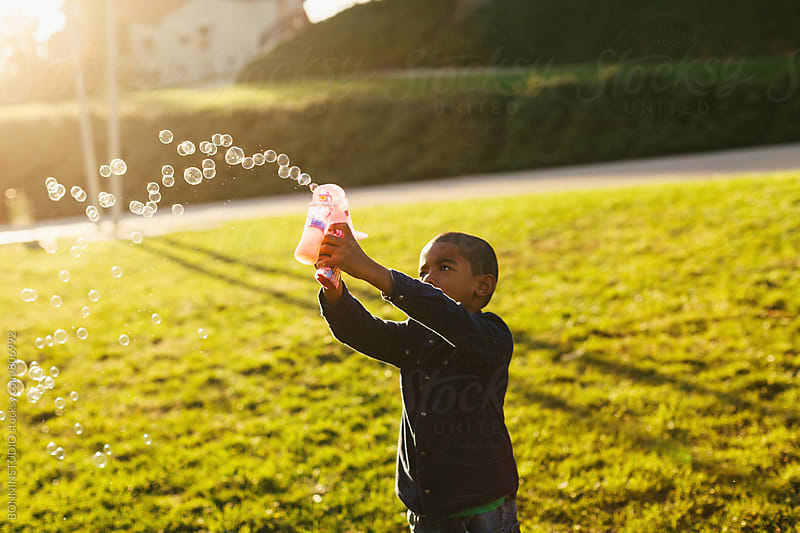 A 5 years old boy playing with soap bubbles in the park. by BONNINSTUDIO for Stocksy United