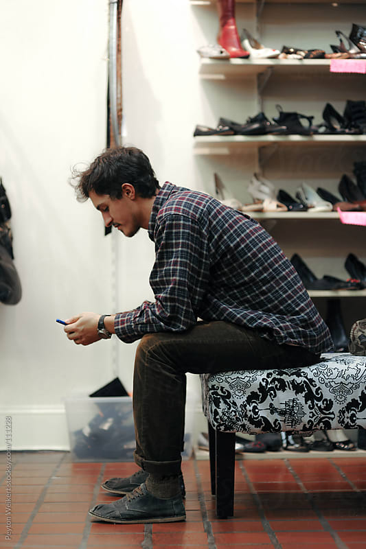 Young man sitting in a store playing on his cell phone by Peyton Weikert for Stocksy United