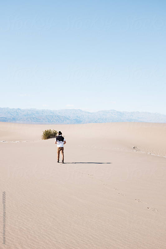 young man walking through desert by Jesse Morrow for Stocksy United