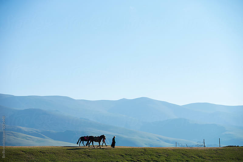 two Tibetan people walking with their horse on the plateau   by Bo Bo for Stocksy United