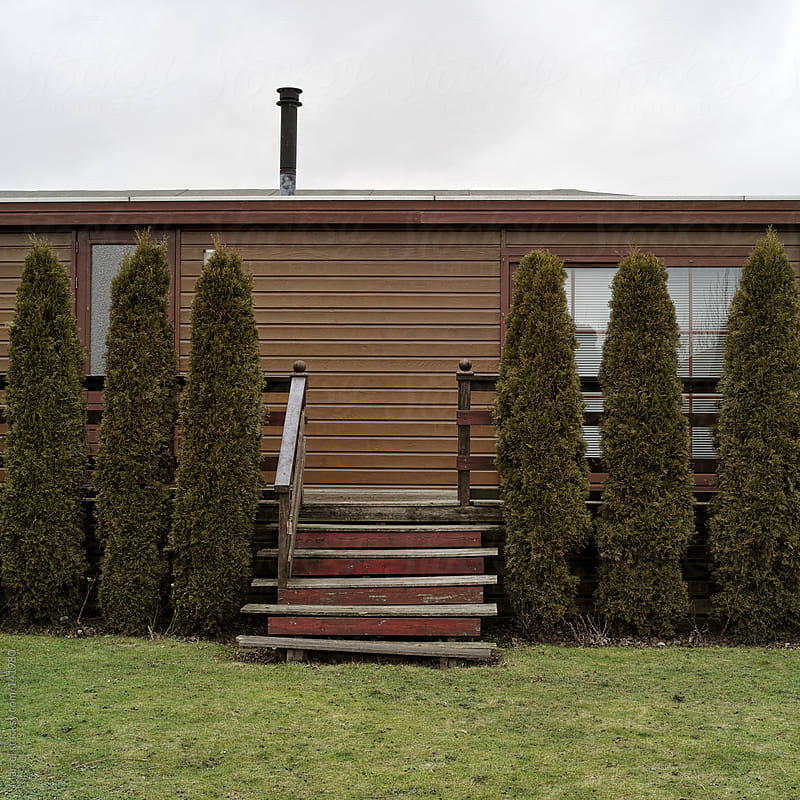 Mobile home behind conifers by Marcel for Stocksy United