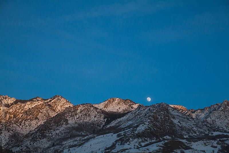 Moonrise over snowy mountains.  by RZ CREATIVE for Stocksy United