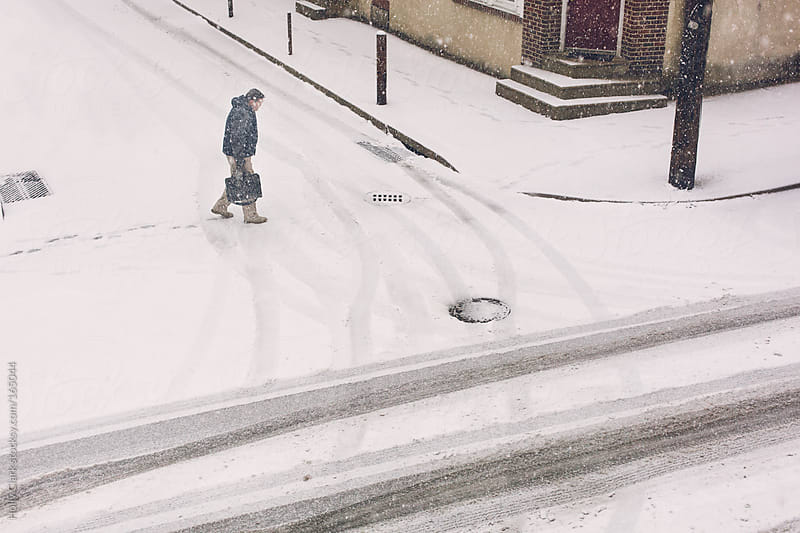 A lone figure crosses a snowy city street. by Holly Clark for Stocksy United