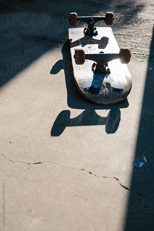 Flipped skateboard on concrete by Curtis Kim for Stocksy United