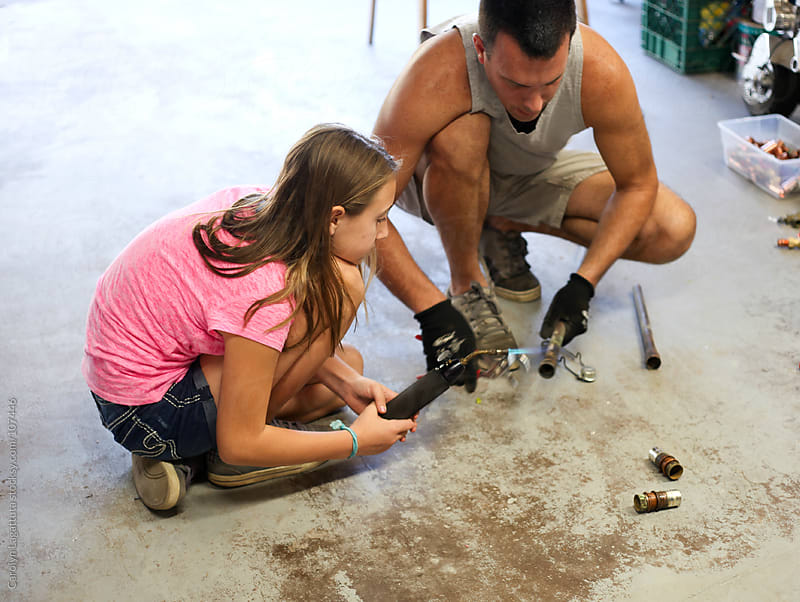 Father and daughter soldering a copper pipe by Carolyn Lagattuta for Stocksy United