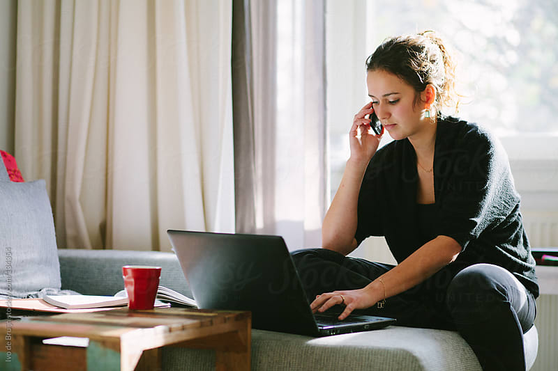 Young woman working from home with a laptop and a cellphone by Ivo de Bruijn for Stocksy United