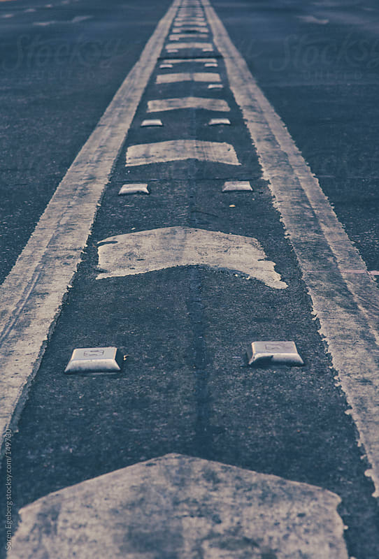 White road markings on black asphalt pavement in the city. by Soren Egeberg for Stocksy United