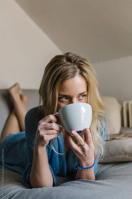 Cute Woman Enjoying a Cup of Tea in Her Living Room by Victor Torres for Stocksy United