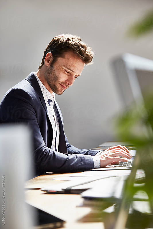 Businessman Using Laptop At Desk by ALTO IMAGES for Stocksy United