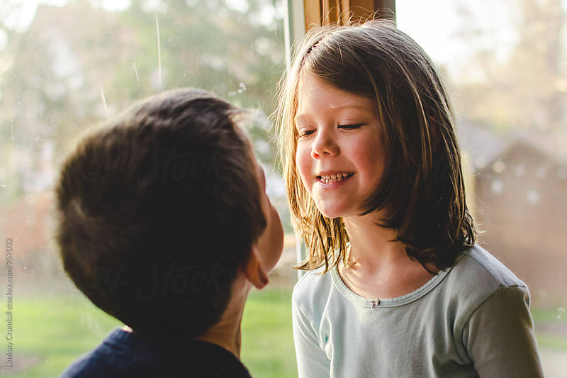 Two children talking to each other by Lindsay Crandall for Stocksy United