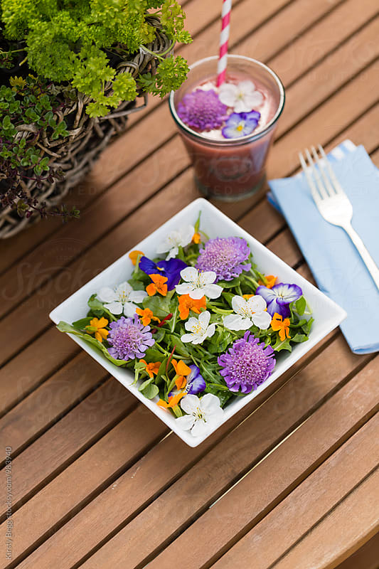 Salad outside with edible flowers and fruit smoothie by Kirsty Begg for Stocksy United