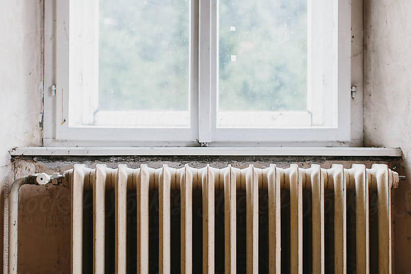 Old cast iron radiator below a window by Amir Kaljikovic for Stocksy United