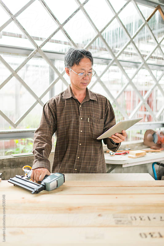 Male Wood Worker Looking at Tablet Computer and Holding Nail Gun in Bright Wood Shop by Lawren Lu for Stocksy United