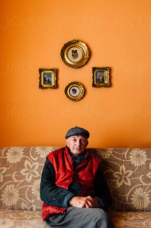 Portrait of senior man sitting on a couch  by Boris Jovanovic for Stocksy United