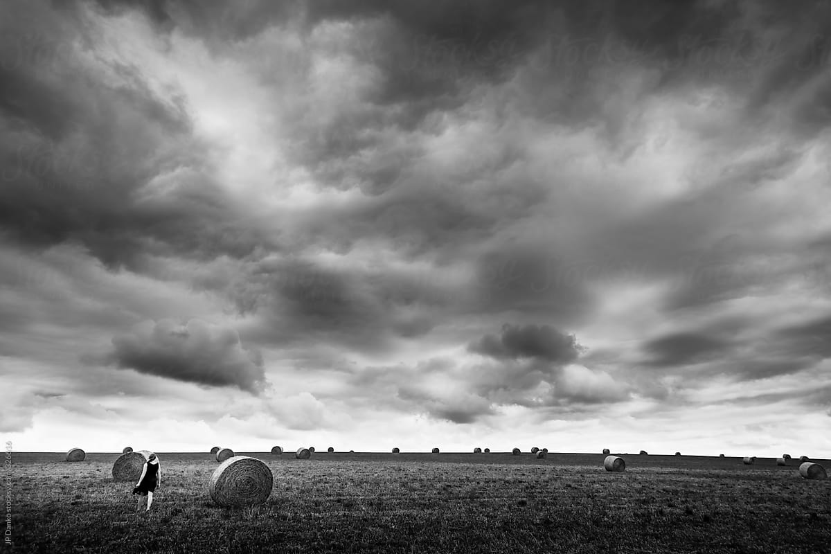 Black and White Woman Walking In Field Under Dramatic ...