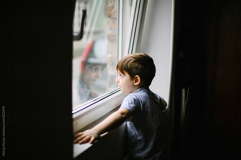 Young boy looking through the window - horizontal by Marija Kovac for Stocksy United