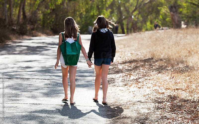 Best friends walking down a path holding hands by Carolyn Lagattuta for Stocksy United