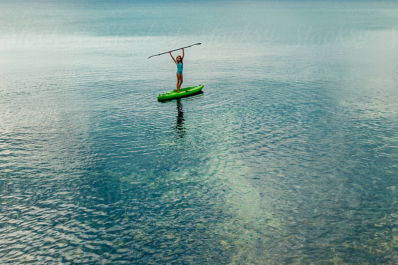 tween girl having fun in the sea with her kayak by Gillian Vann for Stocksy United