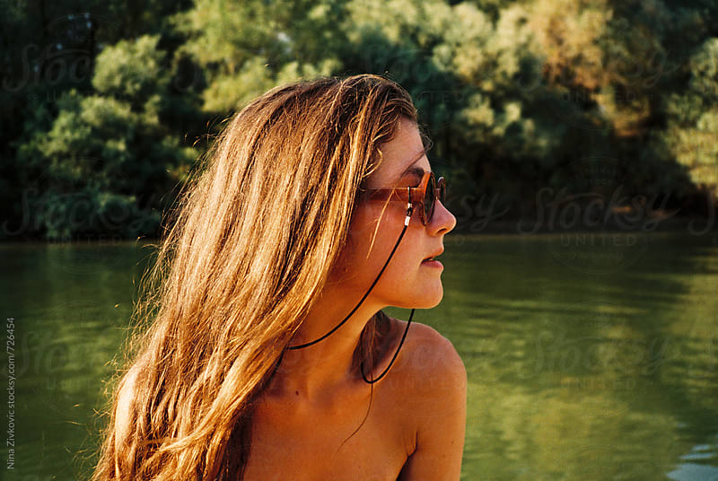 Profile of a young woman wearing sunglasses.  by Nina Zivkovic for Stocksy United