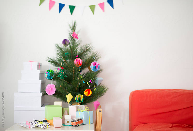 Holiday tree next to red couch by Alita Ong for Stocksy United