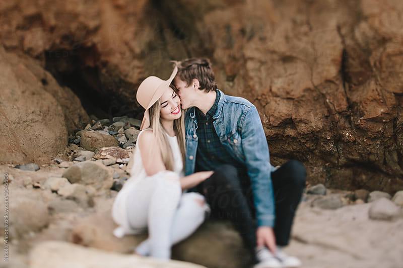 man kissing woman on cheek sitting on beach by Nicole Mason for Stocksy United