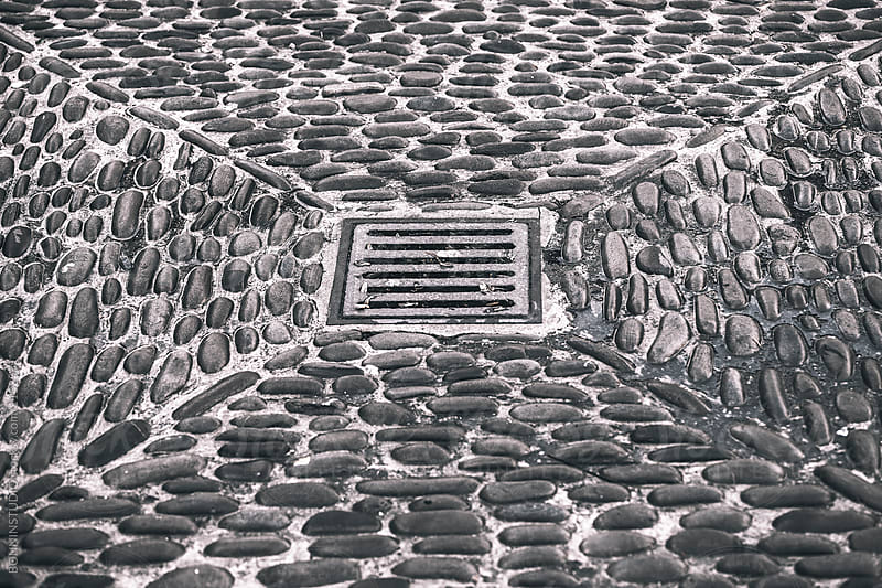 Sewer and river stones in the street. by BONNINSTUDIO for Stocksy United