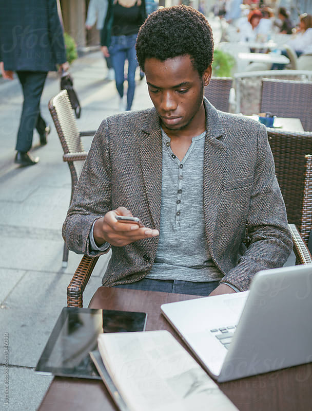 Man Texting in an Outdoor Cafe by Lumina for Stocksy United
