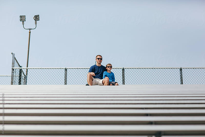 father and son watch an athletic event by Kelly Knox for Stocksy United