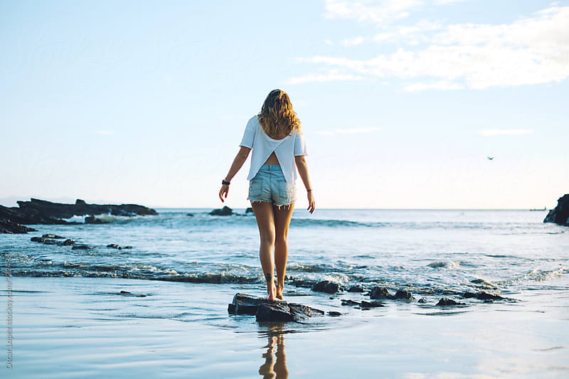 Woman walking on the shore by Oscar Lopez for Stocksy United